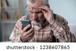 Small photo of Bewildered old man looking at cellphone, new technology complicated for elderly