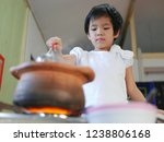 Small photo of Little Asian baby girl enjoys cooking Thai-style hot pot ( Moo Joom )