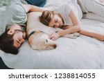 Stock photo pleasant couple sleeping while resting with their dog in bed 1238814055