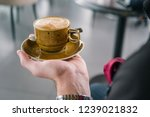 a cup of coffee in the hand of... | Shutterstock . vector #1239021832