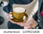 a cup of coffee in the hand of... | Shutterstock . vector #1239021838