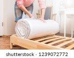 woman unrolling new mattress  | Shutterstock . vector #1239072772