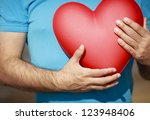 man hands holding big red heart | Shutterstock . vector #123948406