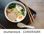 a bowl of shoyu (soy sauce) ramen topped with soft boiled egg, pork wonton, and grilled pork belly