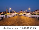 Sopot, Poland. A long wooden pier in Sopot, Poland, with a view of the lighthouse and other old town signature buildings in the night