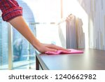 a housewife in a shirt cleans... | Shutterstock . vector #1240662982