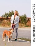 Stock photo woman in walk with his shetland sheepdog dog on leash dog walker standing posing in front of 1240894792