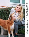 Stock photo beautiful girl with his shetland sheepdog dog sitting and posing in front of camera on wooden bench 1240894795