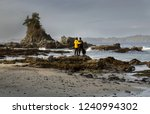 Two Adults Standing On Rocks...