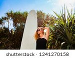 surfer girl in black bikini... | Shutterstock . vector #1241270158