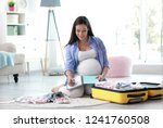 pregnant woman writing packing... | Shutterstock . vector #1241760508