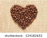 heart shape coffee beans on sacking background - stock photo