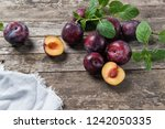 ripe plums on a rustic wooden... | Shutterstock . vector #1242050335