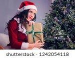 a girl in santa's costume is... | Shutterstock . vector #1242054118
