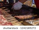 hand of chef cooking meat... | Shutterstock . vector #1242185272