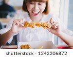 attractive asian woman eating... | Shutterstock . vector #1242206872