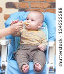 baby is being fed by her mum... | Shutterstock . vector #124222288