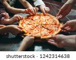 hands taking pizza slices from... | Shutterstock . vector #1242314638