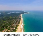 Beach and palm trees with coconuts on beach in Hikkaduwa, Sri Lanka.  Aerial view of town of Hikkaduwa with its beaches, surfspots and buildings. Beautiful tropical beach with great waves for surfing.