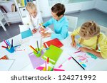Small photo of Trio of friends enjoying drawing in an after-school club