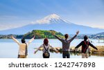 Small photo of Mt diamond fuji with snow and flower garden along the lake walkway at Kawaguchiko lake in japan, Mt Fuji is one of famous place in Japan. People hands up and looking far away.
