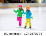 child skating on indoor ice... | Shutterstock . vector #1242870178