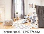 cute boy sitting on bed in... | Shutterstock . vector #1242876682