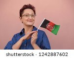 afghanistan flag. woman holding ... | Shutterstock . vector #1242887602