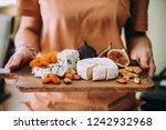 hands holding a wooden board... | Shutterstock . vector #1242932968