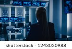Small photo of Female Special Agent Works on a Laptop in the Background Special Agent in Charge Talks To Military Man in Monitoring Room. In the Background Busy System Control Center with Monitors Showing Data Flow.