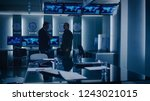 Small photo of Federal Special Agent Talks To Military Man in the Monitoring Room. In the Background Busy System Control Center with Monitors Showing Data Flow.