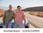 Father and adult son on road trip leaning against their car - stock photo