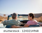 Father and adult son on road trip in open top car, back view - stock photo