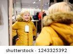 cute little boy trying new coat ... | Shutterstock . vector #1243325392