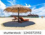 wooden sunbed and umbrella on...   Shutterstock . vector #1243372552