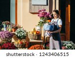 young female florist seller of... | Shutterstock . vector #1243406515