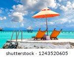 wooden sunbed and umbrella on...   Shutterstock . vector #1243520605