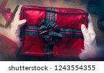 santa claus wrapping a... | Shutterstock . vector #1243554355