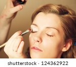 pretty woman applying make up... | Shutterstock . vector #124362922