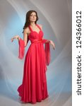 Beautiful young woman in red evening dress, on grey background - stock photo