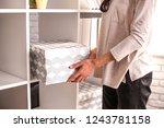 woman put a cardboard box on... | Shutterstock . vector #1243781158