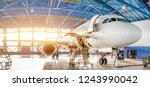 Stock photo maintenance and repair of aircraft in the aviation hangar of the airport view of a wide panorama 1243990042