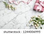Stock photo flat lay composition with beautiful roses and gift box on marble background space for text 1244006995