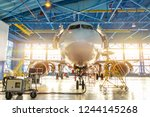 Stock photo aircraft in the aviation industrial hangar on maintenance outside the gate bright light 1244145268