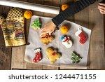 baby hand picks up gingerbread... | Shutterstock . vector #1244471155