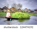 INLE LAKE, MYANMAR - NOVEMBER 5, 2012 ; A woman has a boat full of reet from the floating gardens on November 5, 2012 Myanmar. The Inle Lake is famous for these floating gardens and his ecosystem - stock photo