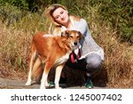 Stock photo pretty girl with his shetland sheepdog dog at nature park outdoor is standing and posing in front 1245007402