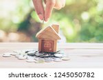 house placed on coins. hand... | Shutterstock . vector #1245050782