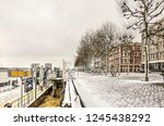 Small photo of Rotterdam, The Netherlands, December 11, 2017: Willemskade quay and the waterbus stop covered with a thin layer of snow on a cold winter day by the Nieuwe Maas river