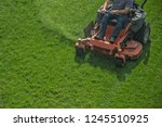 Closeup of a riding landscaper on the lawn mower cutting the grass - stock photo